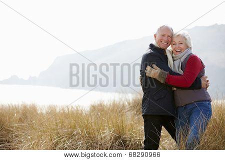 Senior Couple Walking Through Sand Dunes On Winter Beach