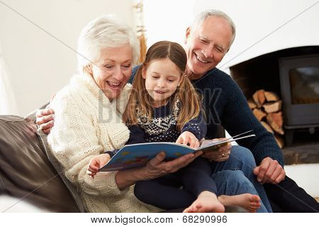 Grandparents And Granddaughter Reading Book At Home Together