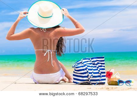 back view of a woman with stripy bag and straw hat at tropical beach