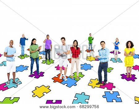 Multi-ethinic people standing on puzzle pieces while social networking via modern technology