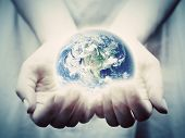 The earth shines in young woman hands. Concepts of save the world, protection, taking care, environment. Elements of this image furnished by NASA poster