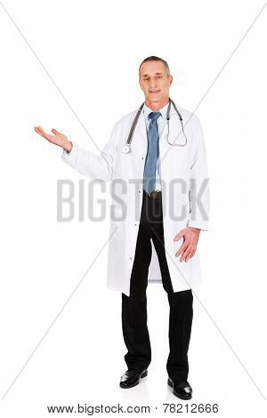 Full length male doctor holding copyspace in right hand.