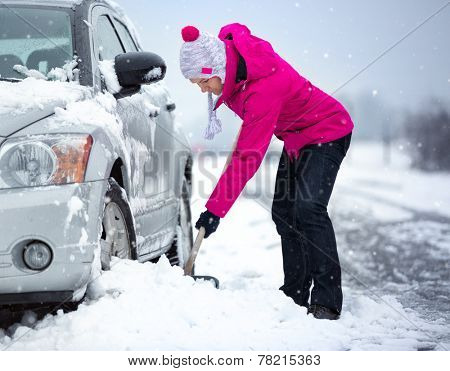 woman shoveling and removing snow from her car, stuck in snow