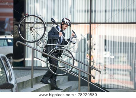 businessman with a cycle helmet on head carrying his bike down steps