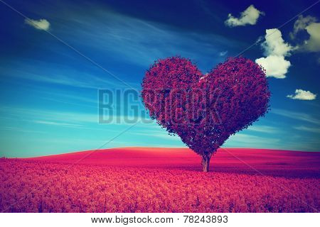 Heart shape tree with red leaves on red flower field. Love symbol, concept for Valentine's Day, wedding etc. Vintage style