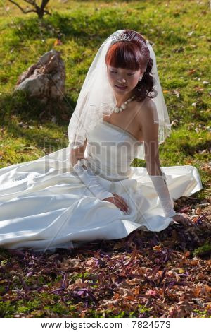 Beautiful Bride On Ground With Autumn Leaves