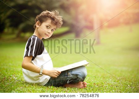 Young pan asian boy enjoying his reading book in outdoor park