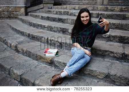 Young charming girl smiling while taking a self-ie outdoors young tourist woman taking a self portrait with smart phone in Barcelona beautiful young hipster girl photographing herself with phone poster