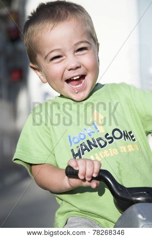 Handsome little boy rides toy motorbike, outdoor