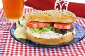 Fresh and healthy tuna salad sandwich on a sesame bagel. Chips and potato salad sides and a glass of ice tea. poster