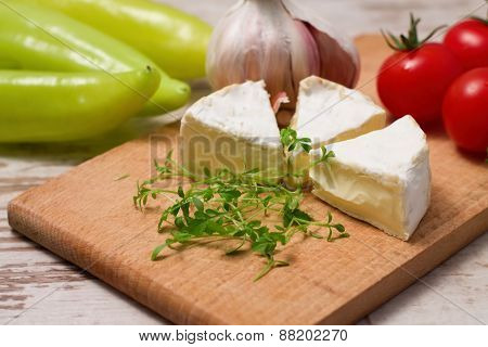 Three Portions Of Camembert And Cress On Wooden Board