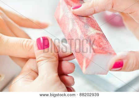 Nail treatment at beauty salon, beautician brushing fingernail poster
