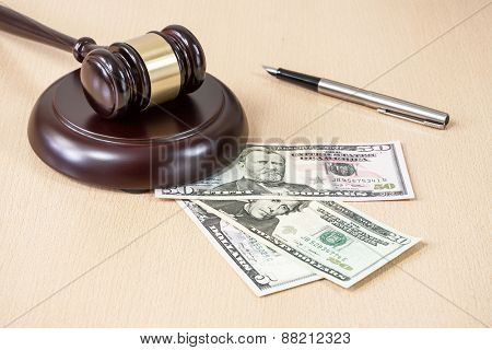 A wooden gavel on wooden table, on brown background, dollars