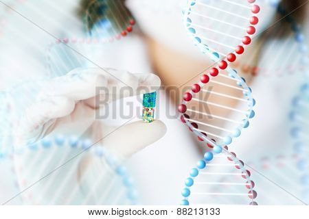 science, chemistry, biology, medicine and people concept - close up of young female scientist or doctor showing pill in laboratory and dna molecule structure