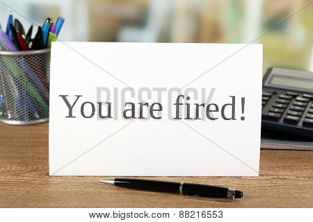 Message You're Fired on wooden table, closeup