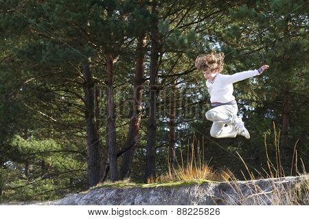 Boy Jumping From Sand Dunes In Pinewood Forest