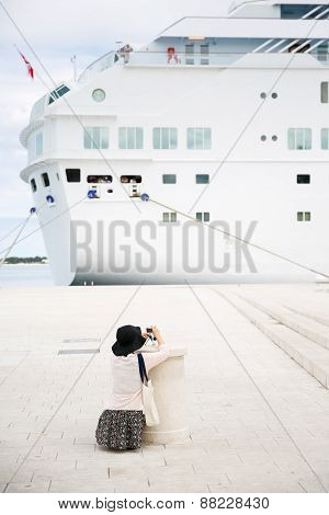 Tourist and passenger photographing a big cruise ship docked in port for necessary maintenance refill of supplies and sightseeing tour. Travel hospitality and cruising business concept. poster