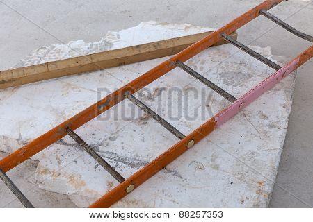 A orange steel ladder ontop of a concrete slab on a construction site