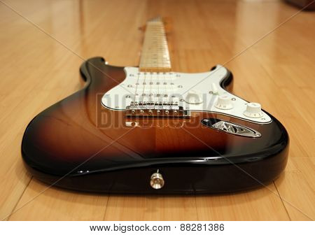An electric guitar laying on wooden floor