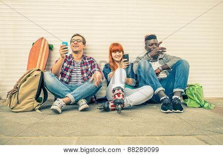 Group of friends of different ethnics sitting on the street and looking at mobile phone - Young modern hipster people having fun with new technologies - Multiracial group representing the addiction to technology poster