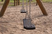 Empty swing on children playground in city poster