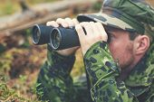 hunting, war, army and people concept - young soldier, ranger or hunter with binocular observing forest poster