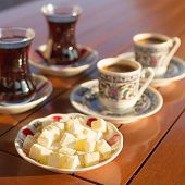Locum turkish coffee and turkish tea in outdoor cafe. Direct sunset light. Shallow DOF and lightly toned poster