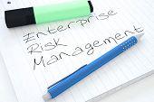 Enterprise Risk Management - handwritten text in a notebook on a desk - 3d render illustration. poster