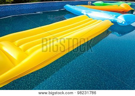 Multicolored air mattresses floating on the calm surface of a smaller pool