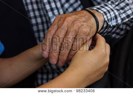 Nephew Wire Up The Friendship Band To Grandfather's Hand