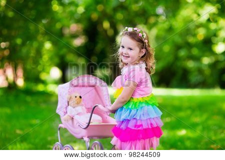 Little Girl Pushing A Toy Stoller Wth Doll