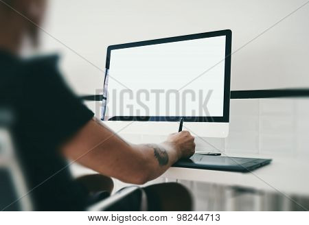 Man at workspace with generic design computer on the table.
