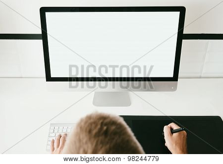 Man in his workspace with generic design computer