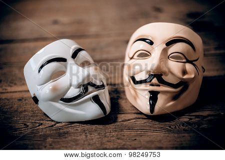 white and yellow anonymous masks on wood background - retro style