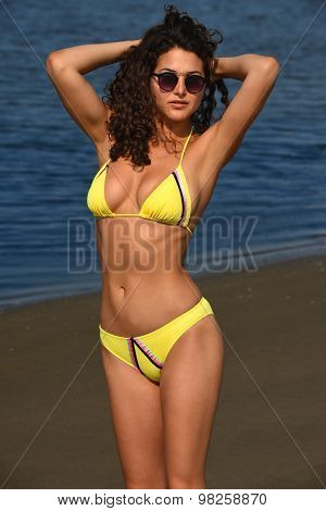 Woman in yellow bikini and sunglasses posing on the beach