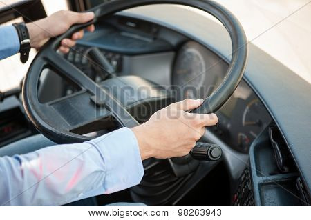 Young skilled man is driving a public transport
