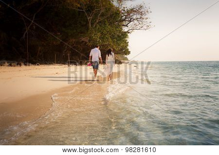 brunette bride and groom walk barefoot along edge of transparent water poster