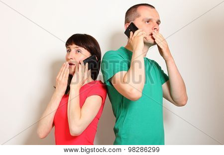Shocked woman and man receive an unexpected message while talking on mobile phone hands covering mouth face expression and human emotionon poster