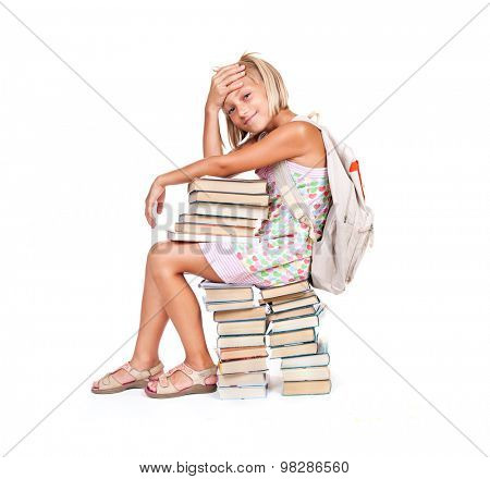 Back to school. Tired Schoolgirl with rucksack and stack of books isolated on a white background. Education concept, knowledge. Full length portrait of School girl sitting on stack of books