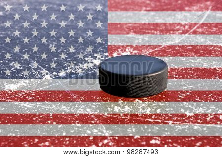 Black hockey puck on ice rink with flag of the United States