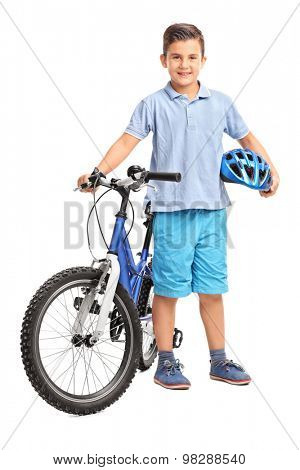 Full length portrait of a little kid posing with his bicycle and holding a blue helmet in his hand isolated on white background