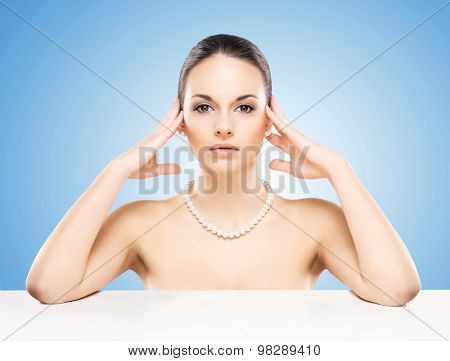 Portrait of young, beautiful and healthy woman in a pearl necklace