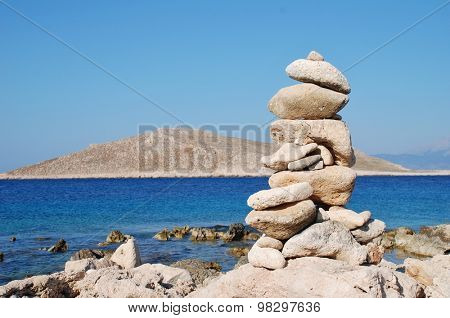 A pile of stones on Ftenagia beach at Emborio on the Greek island of Halki. The uninhabited island of Nissos is in the background.