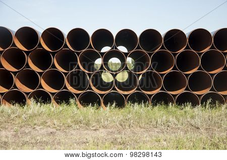 closeup of a pile of large and rusting steel pipes poster