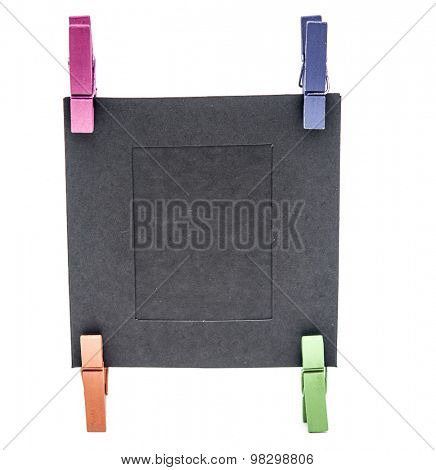 Blank paper frame and colorful clothespins isolated on white