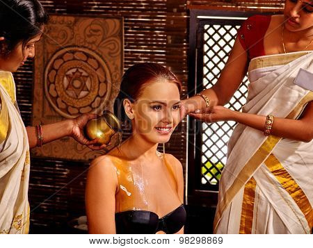 Woman having Ayurvedic treatment. Pouring milk.Spa resorts in India