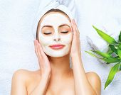 Spa Woman applying Facial cleansing Mask. Beauty Treatments. Clay mask poster