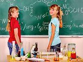 Happy kids holding flask in school class. Children's chemistry  poster
