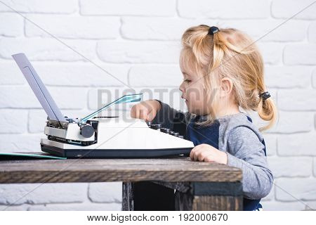 Small Boy Sitting At Table And Typing Typewriter With Paper