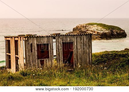 A shed in the coast with an small island on the background. Northern Spain.